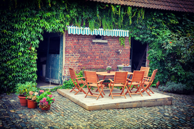 Bauernhofhinterhof mit Tabelle und Stühlen stockfotos