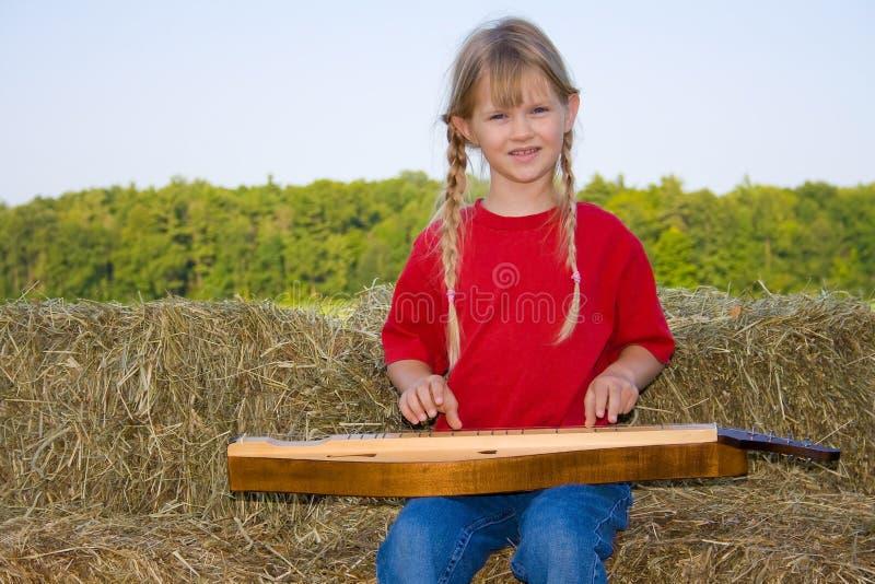 Bauernhofmädchen, das eine Mandoline spielt. lizenzfreie stockbilder
