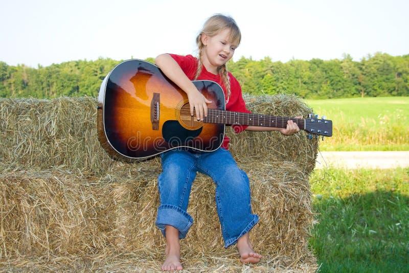 Bauernhofmädchen, welches die Gitarre klimpert. lizenzfreies stockfoto