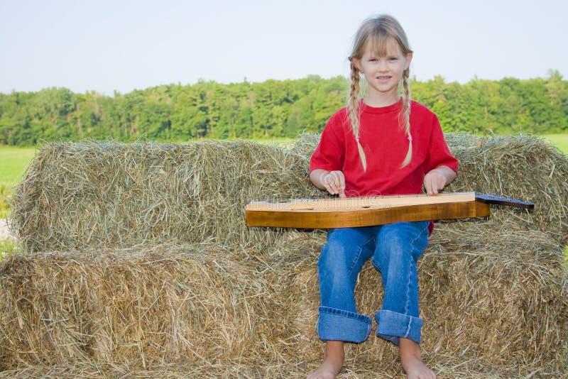 Bauernhofmädchen, welches die Mandoline spielt. stockfotos