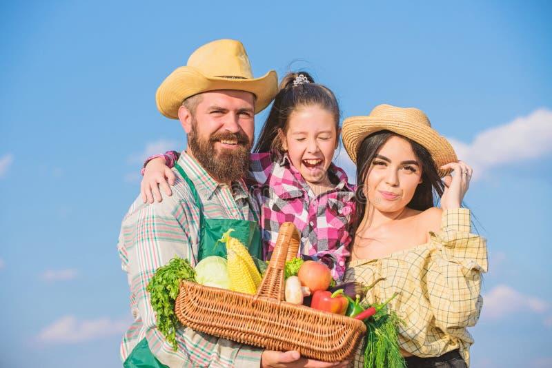 Bauernhofmarkt mit b?rtigem rustikalem Landwirt Fallernte Mannes mit Kind und Frau Familienvaterlandwirt-Mutterg?rtner mit stockbilder