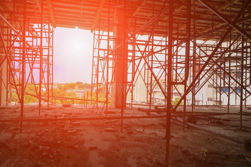 Baugerüststahlkonzernschattenbild im ArbeitsBaustellegebäude mit Sonnenunterganglicht stockbild