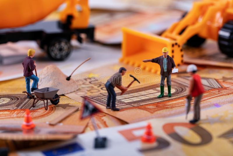 Baugewerbekonzept - Arbeitskraftteam, das schwer arbeitet, um mehr Geld zu erwerben lizenzfreie stockbilder