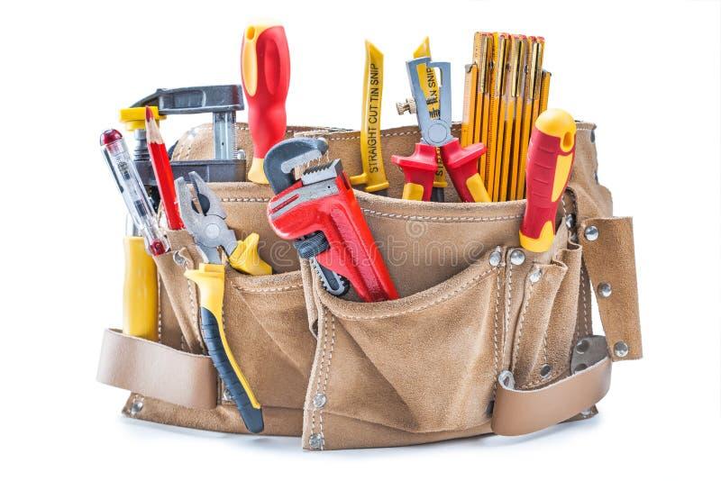 Bauhandwerkzeuge im braunen ledernen Werkzeuggurt lokalisiert auf Weiß lizenzfreies stockfoto