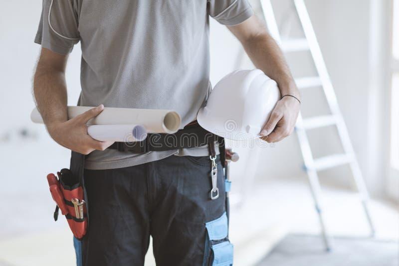 Bauingenieur, der Schutzhelm und Projekte hält stockfoto