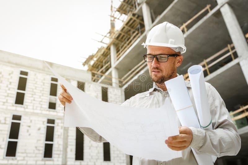 Bauingenieur in einem weißen Hardhat, der Pläne O kontrolliert lizenzfreie stockbilder