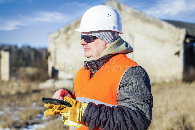 Bauingenieur mit nahem zerstörtem Gebäude des Tablet-PCs stockfotos