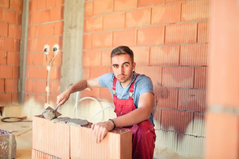 Bauingenieur und Arbeitskraft, die ein Haus bauen, Backsteinmauern mit Mörser erneuern und herstellen lizenzfreie stockbilder