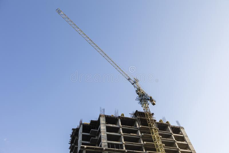 Baukran mit hohem Gebäude im Bau lizenzfreies stockfoto