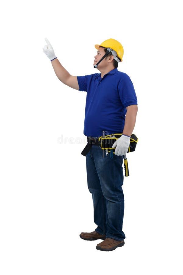 Baumannarbeitskräfte im blauen Hemd mit Schutzhandschuhen, im Sturzhelm mit Werkzeuggurt und im Finger zeigend oben lokalisiert a stockbilder