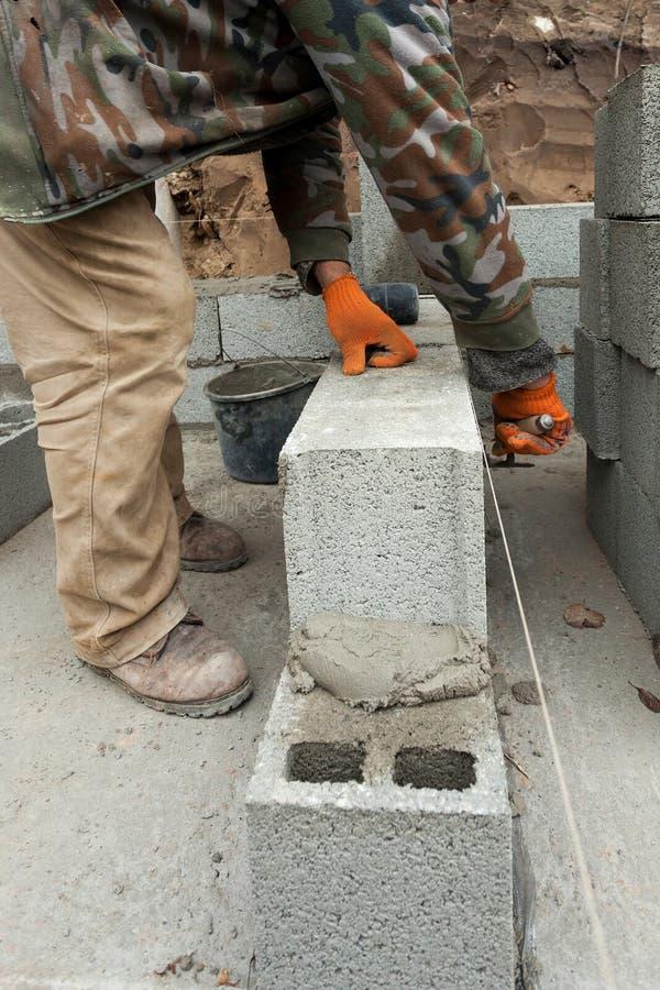 Baumaurer-Arbeitskraftmaurer, der draußen Betonblockgrundmauer mit Spachtel legt lizenzfreie stockbilder