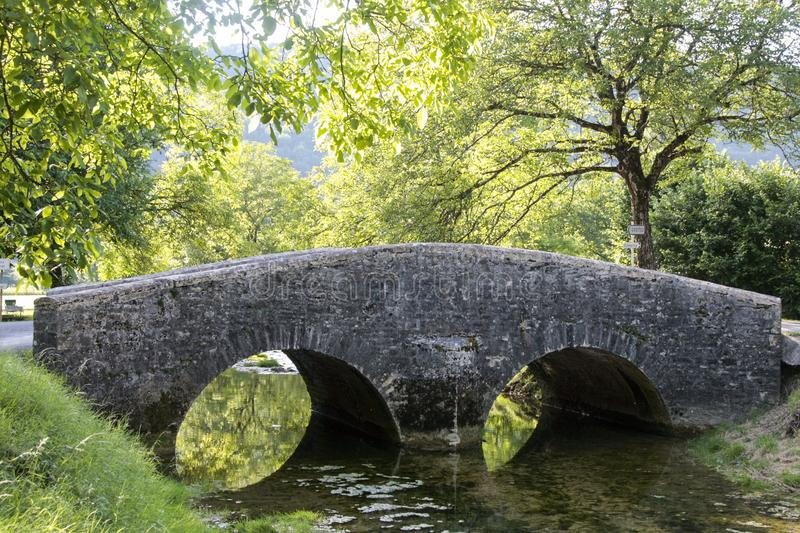 Old bridge near medieval village of Baume les Messieurs in France stock image