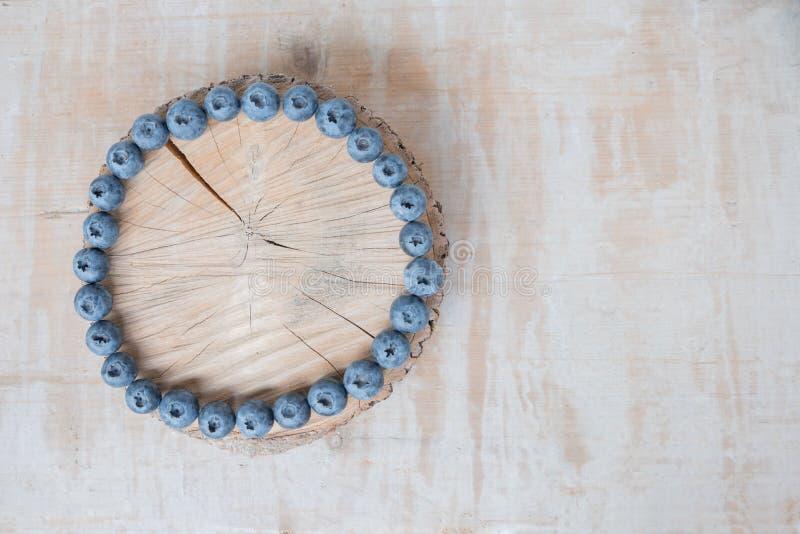 Baumscheibe gestaltet mit Blaubeeren auf hölzernem Hintergrund der Weinlese lizenzfreie stockfotografie