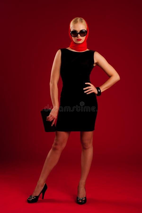 Baumuster im schwarzen Kleid über rotem Hintergrund lizenzfreies stockbild