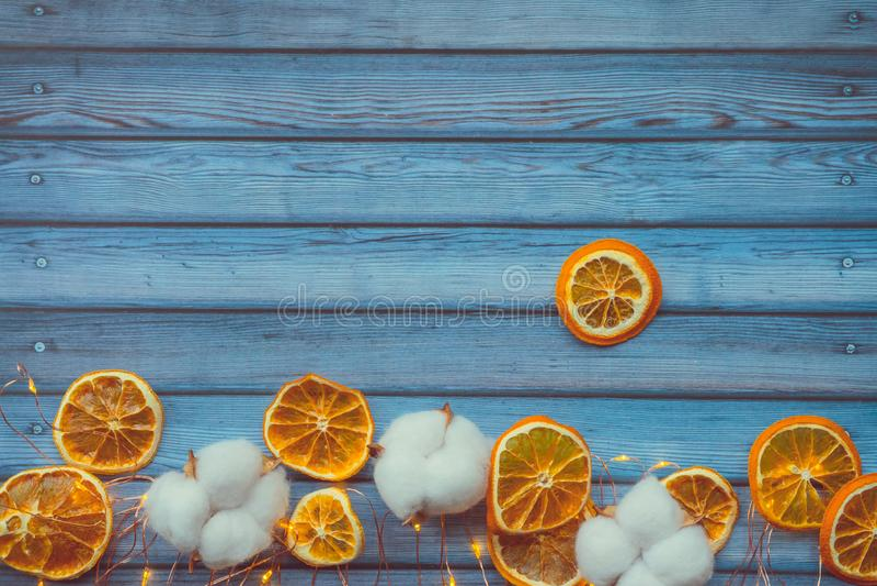 Baumwollkapseln und dired Orangen auf blauem Holztisch stockbild