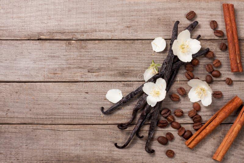 A baunilha cola com os feijões da canela e de café em um fundo de madeira velho com espaço da cópia para seu texto Vista superior fotografia de stock