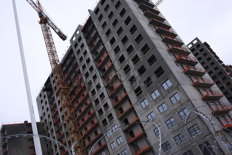Bauphasen eines mehrst?ckigen Geb?udes Das Gie?en des Betons und Aufrichtung von Plattenb?den Details und Nahaufnahme stockbild