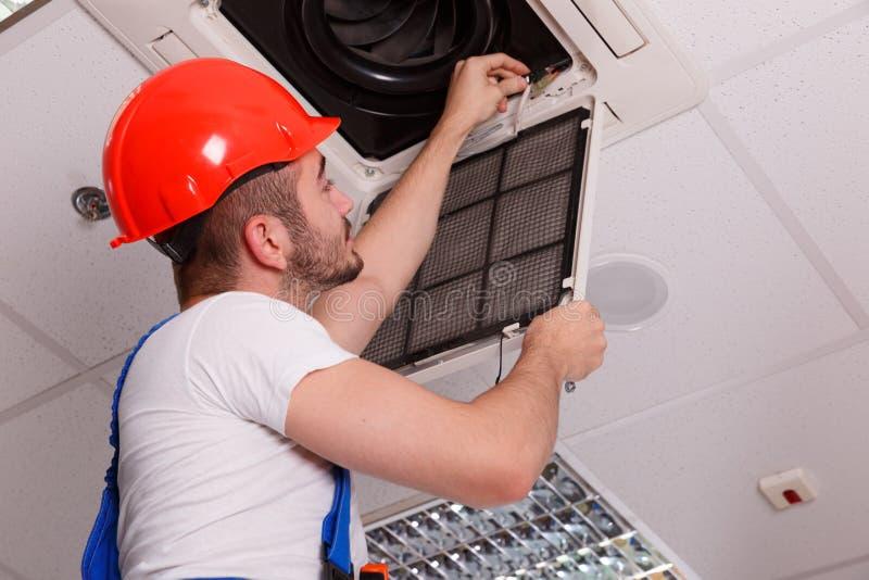 Bauschlosser überprüft die Verdrahtung auf Belüftung im Raum stockfotos