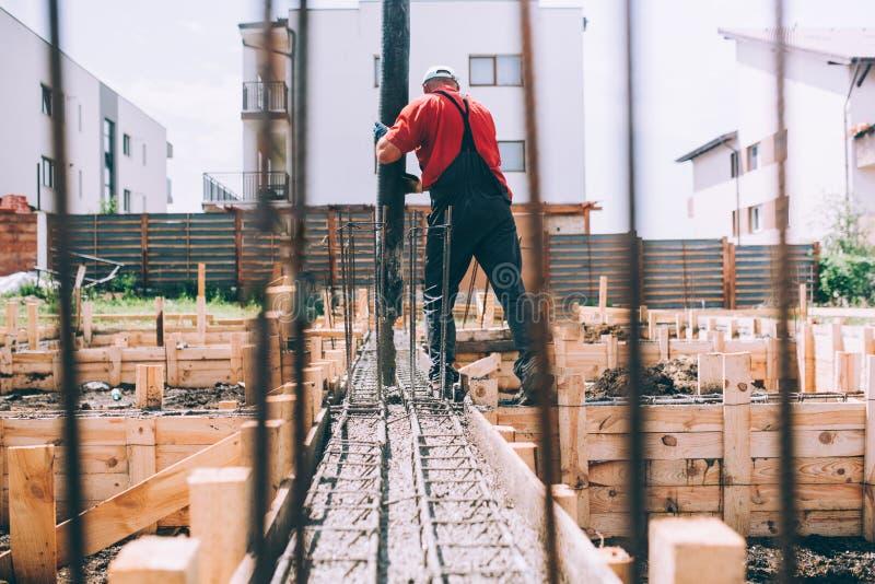Baustelle-Arbeitsdetails - Gebäudehaus und Anwendung der Betonpumpe stockfoto