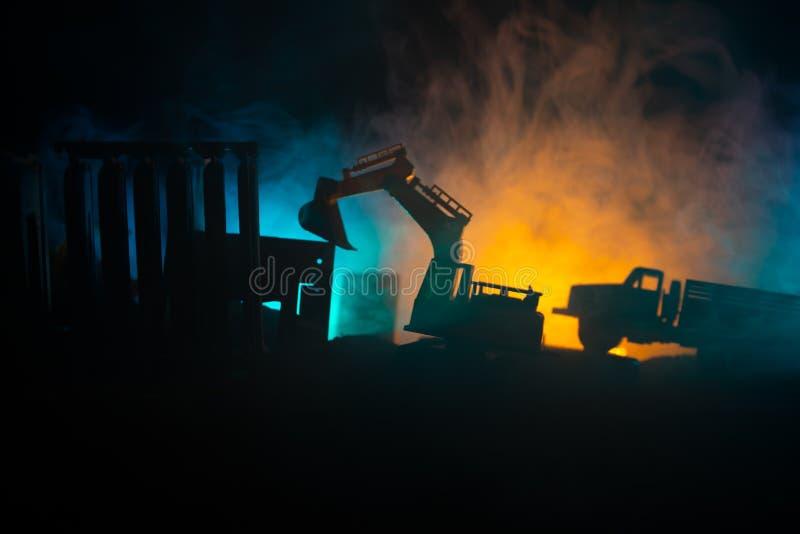 Baustelle auf einer Stadtstraße Ein gelber Baggerbagger parkte während der Nacht auf einer Baustelle Industrielles Konzept t lizenzfreie stockbilder