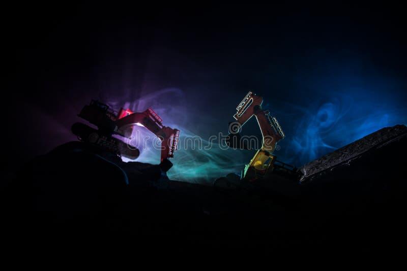 Baustelle auf einer Stadtstraße Ein gelber Baggerbagger parkte während der Nacht auf einer Baustelle Industrielles Konzept t stockfotos