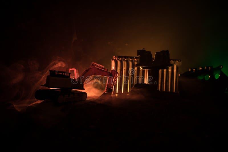 Baustelle auf einer Stadtstraße Ein gelber Baggerbagger parkte während der Nacht auf einer Baustelle Industrielles Konzept t stockfotografie