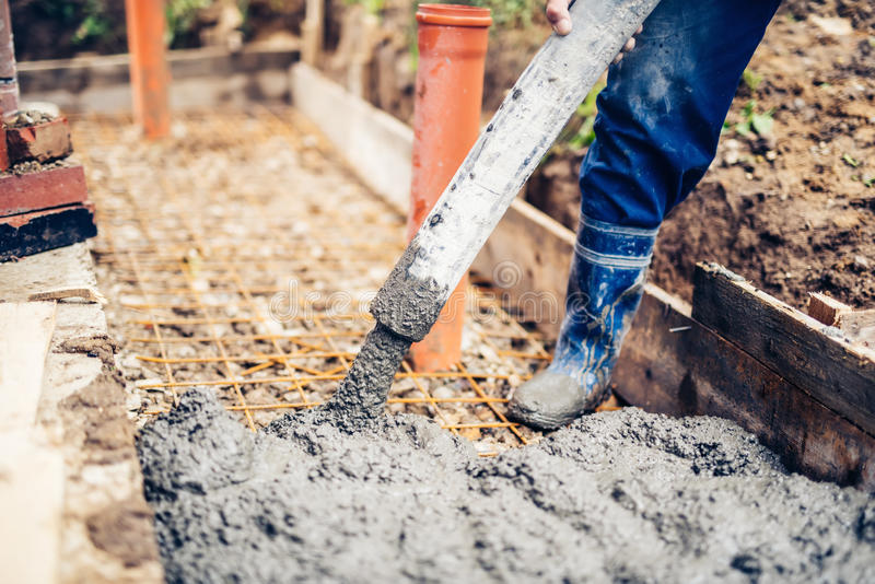 Baustelle - Gebäudebürgersteige und auslaufender Zement auf Verstärkungsstangen stockfotografie