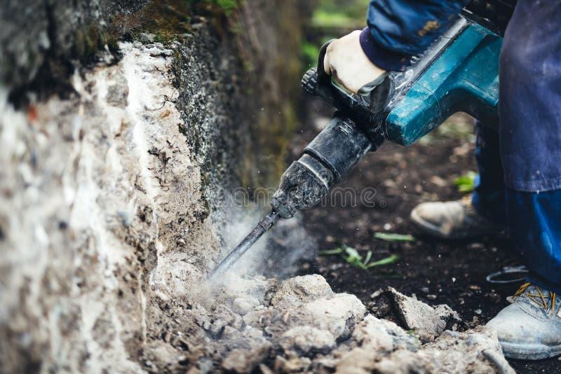 Baustelle mit der Arbeitskraft, die pneumatischen Jackhammer für die Zerstörung einer Tragmauer verwendet stockfoto