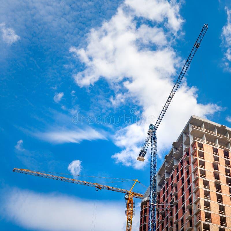 Baustelle mit Kränen gegen einen blauen Himmel mit weißen Wolken stockbilder