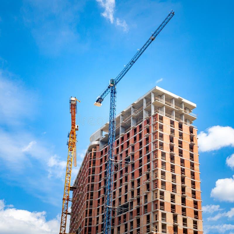 Baustelle mit Kränen nahe dem Gebäude gegen den blauen Himmel mit weißen Wolken stockbilder
