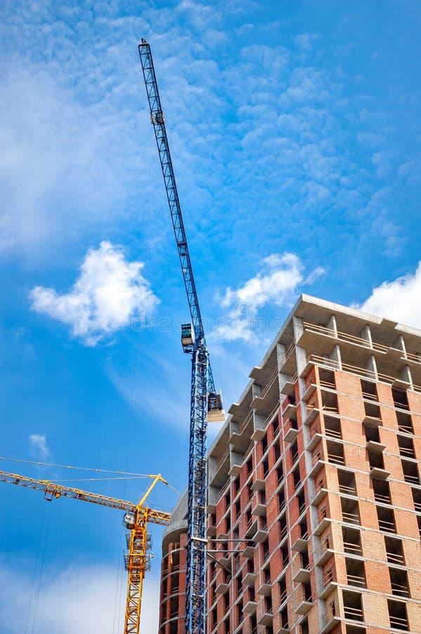 Baustelle mit Kränen nahe dem Haus gegen den blauen Himmel mit weißen Wolken lizenzfreies stockbild