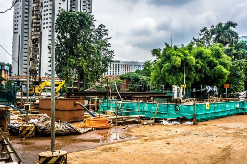 Baustelle mit Materialien und Ausrüstungen nahe hohem Aufstiegsgebäude Foto eingelassenes Jakarta Indonesien stockfotos