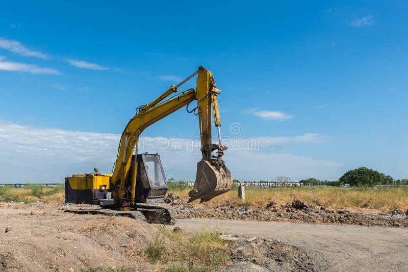 Baustelle mit schmutzigem gelbem Bagger während der Arbeit stockbilder