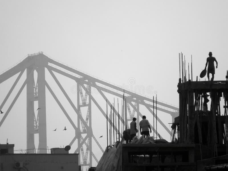 Baustellearbeitskräfte mit Howrah-Brückenhintergrund lizenzfreie stockfotografie