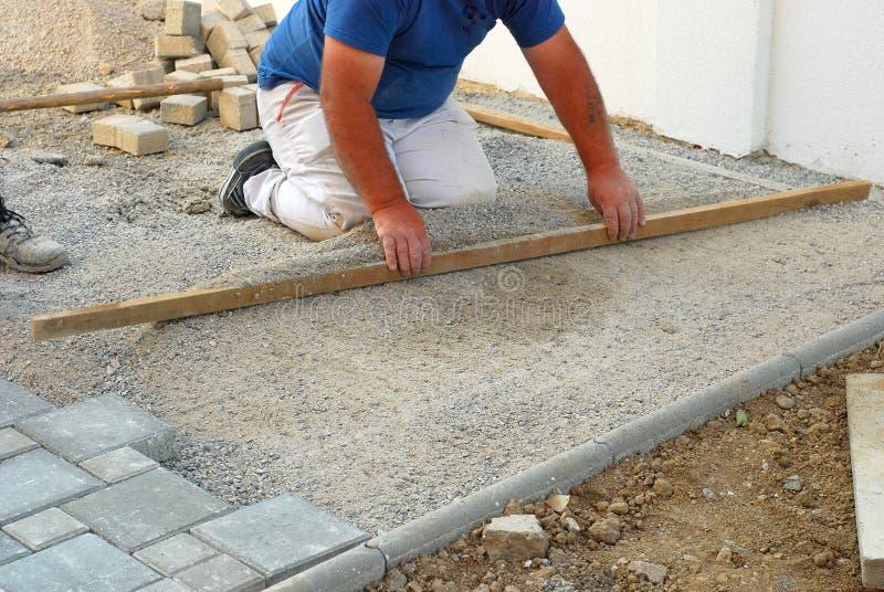 Baustellearbeitskraft, die den Sand während der Installierung der konkreten Ziegelsteinpflasterung planiert stockbild
