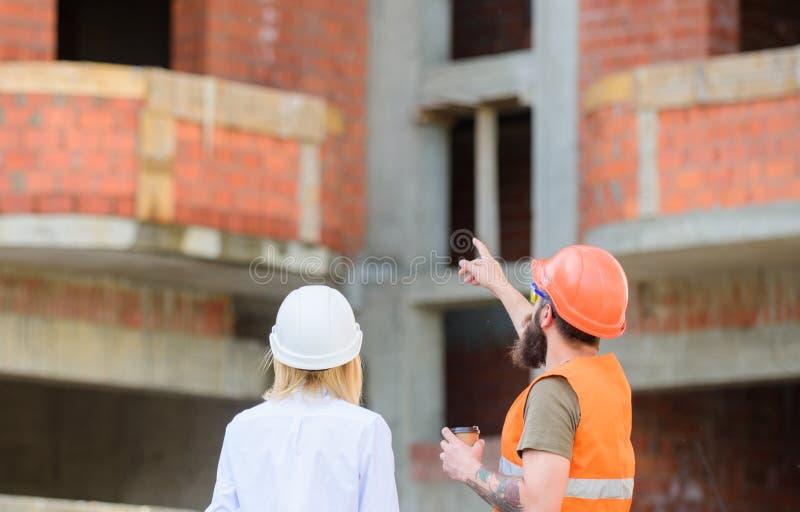 Bauteam-Kommunikationskonzept Behandeln des Planes Fraueningenieur und -erbauer stehen an der Baustelle in Verbindung stockbild
