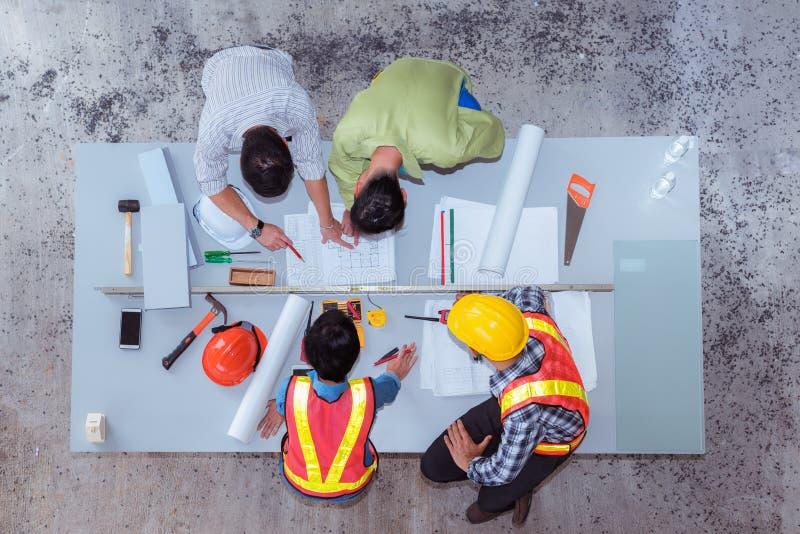 Bauteamarbeit, sie ` bezüglich des Sprechens über neues Projekt, Spitzenv lizenzfreie stockfotografie