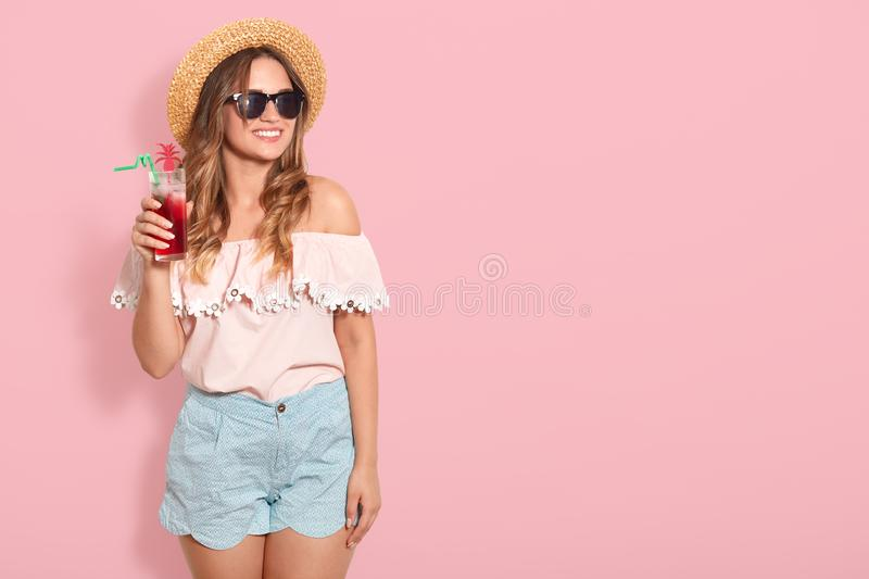 Bautiful girl in sunglasses, straw hat, summer blouse and short drinking summer cocktail, looking smiling aside, posing  royalty free stock photo