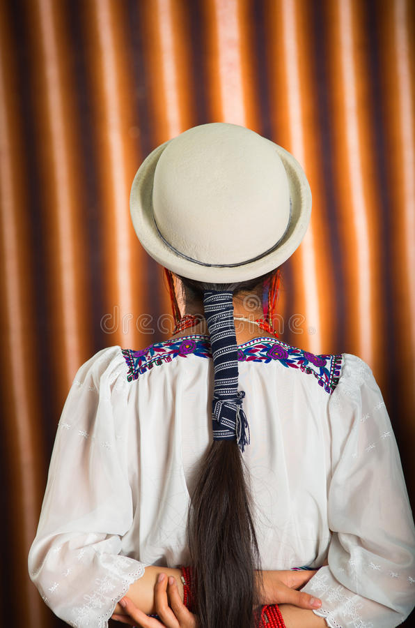 Bautifully ha vestito il modello ispanico che indossa l'abbigliamento tradizionale andino con il cappello bianco di corrispondenz immagine stock