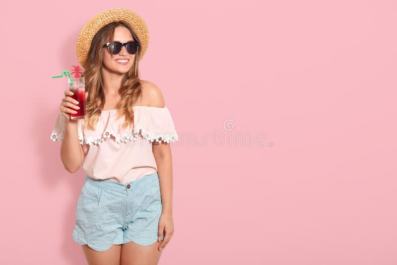 Bautifulmeisje die in zonnebril, strohoed, de zomerblouse en korte het drinken de zomercocktail, opzij glimlachend, het stellen k royalty-vrije stock foto