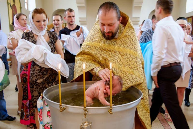 bautismo de un niño en una iglesia cristiana en una fuente foto de archivo libre de regalías
