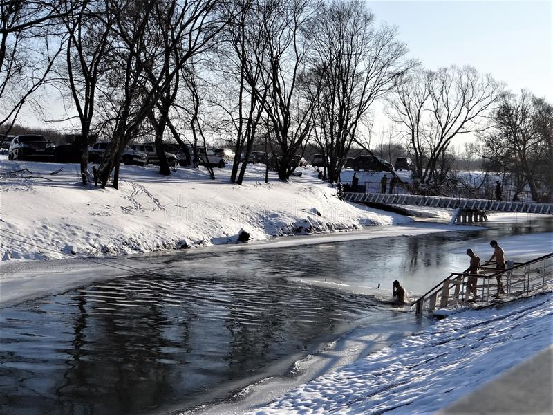 Bautismo, mañana escarchada, bañando a gente en el río fotos de archivo libres de regalías