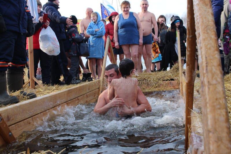 Bautismo ortodoxo del día de fiesta en Rusia una muchedumbre de zambullida desnuda de la gente en el agua helada en invierno homb fotografía de archivo