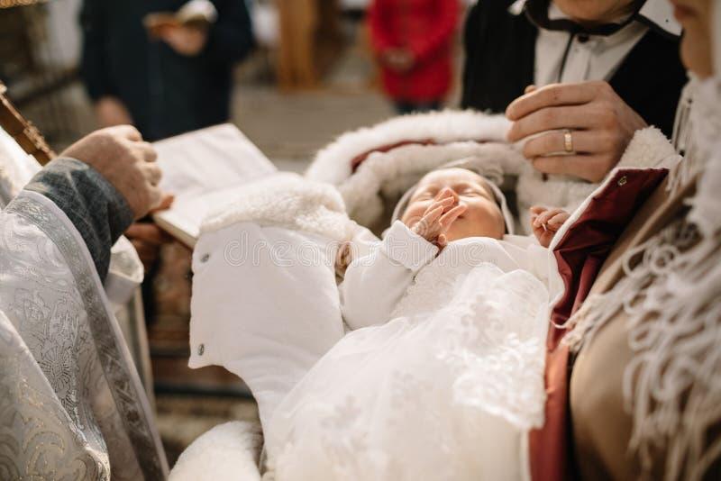 Bautizo del pequeño bebé en la iglesia, los pies y el sacerdote h del primer imagen de archivo