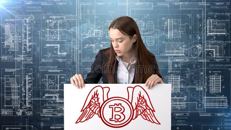 Bauty站立在与Bitcoin商标的衣服的女商人说明使用换或汇款的bitcoin 免版税库存图片