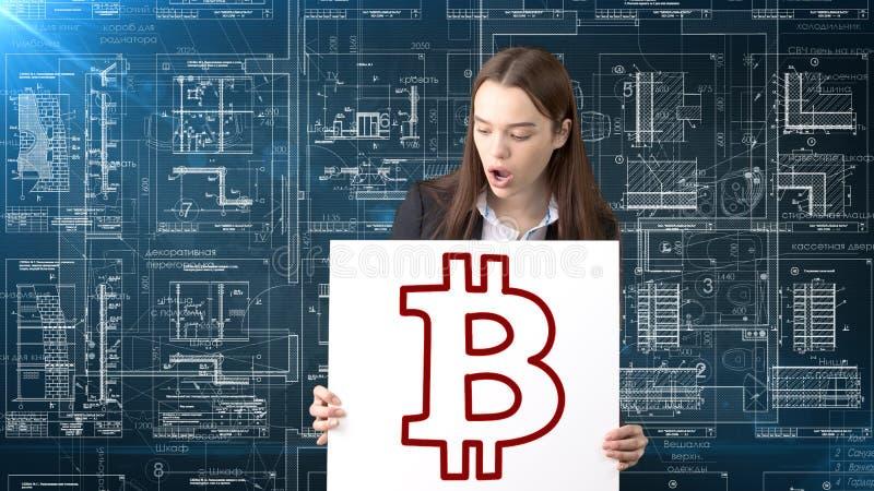 Bauty站立在与Bitcoin商标的衣服的女商人说明使用换或汇款的bitcoin 库存图片