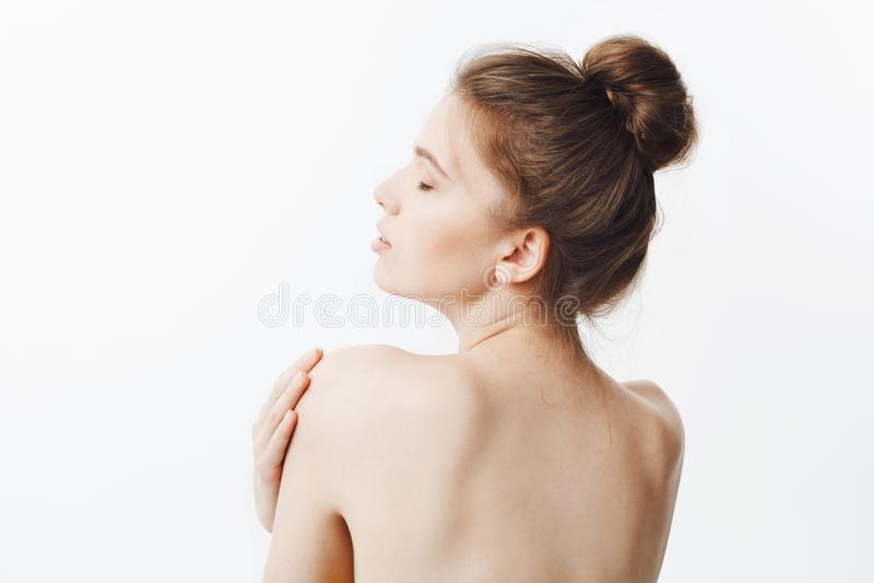 Bauty και υγεία Όμορφο λεπτό υγιές καυκάσιο κορίτσι με τη σκοτεινή τρίχα στο κουλούρι hairstyle και γυμνό δέρμα, στροφές με στοκ φωτογραφίες