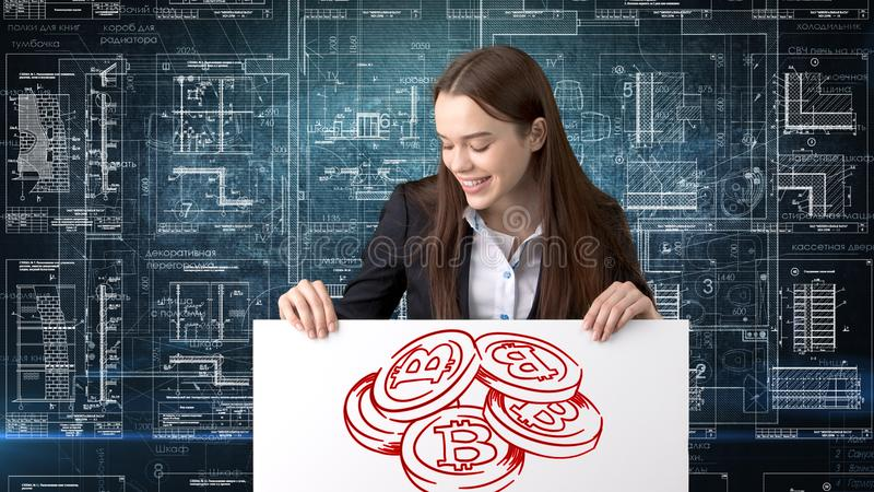 Bauty business woman standing in suit with Bitcoin Logo to illustrate the use of bitcoin for trading or money transfer. royalty free stock image