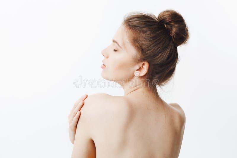 Bauty och hälsa Snygg tunn sund caucasian flicka med mörkt hår i bullefrisyren och naken hud, vänd med arkivfoton