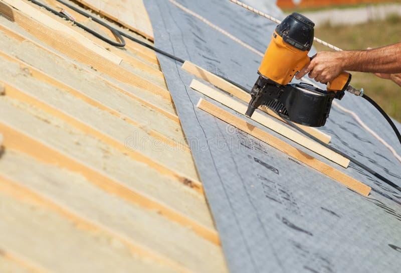 Bauunternehmer-Arbeitskraft Roofer mit einem Luftnagel-Gewehrnägelhersteller, der an dem Dach auf einem neuen Haupt-constructiion lizenzfreie stockfotografie